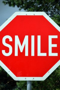 Red and White Sign Smile and the World smiles with you