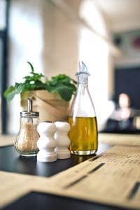 Bottle of Oil on counter next to white salt and pepper pot