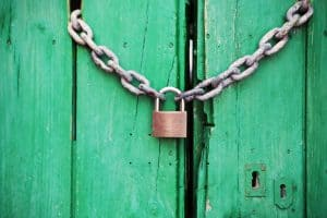 Brass-colored Metal Padlock With Chain on green wooden door