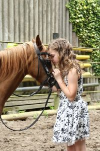Young girl kissing head of a brown horse