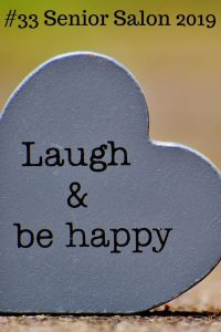 Words Laugh & be happy on a gray heart shape stone